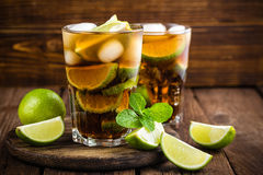 Cuba Libre cocktail with cola, lime and ice in glass, cold longdrink. On wooden background royalty free stock photos
