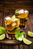 Cuba Libre cocktail with cola, lime and ice in glass, cold longdrink. On wooden background stock photos
