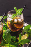 Cuba Libre cocktail with cola, lime, rum and peppermint royalty free stock photo