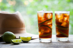 Cuba Libre cocktail with lime, ice, mint and rum on wooden table with a straw hat and view to the terrace. Close up stock image