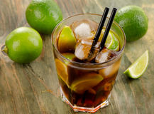 Cuba Libre cocktail with limes Royalty Free Stock Photography
