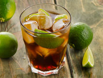 Cuba Libre cocktail with limes on a wooden Royalty Free Stock Photos
