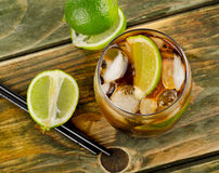 Cuba Libre Drink with lime on a wooden table Royalty Free Stock Images