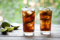 Cuba Libre refreshing summer cocktail with a cola, ice, lime and rum on wooden table with a view to the terrace and. Trees. Close up summer beverage. Cold royalty free stock image