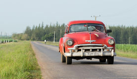 Cuba red american classic car drives on the street in the province Stock Images