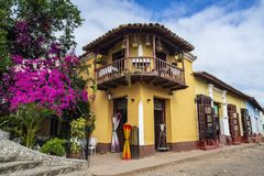 Cuba Trinidad. Corner of old two floor building restaurant with violet and purple flowers. Beautiful sky with clouds royalty free stock images