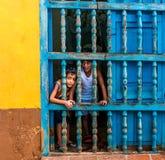 Cuba, Trinidad Em junho de 2016: Duas crianças que olham fora da janela de sua casa em Trinidad fotos de stock
