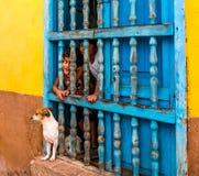 Cuba, Trinidad Em junho de 2016: Duas crianças que olham fora da janela de sua casa em Trinidad, igualmente um cão estão na janel Fotos de Stock Royalty Free
