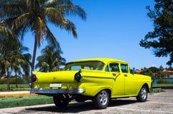 Cuba yellow classic cars in havana. Cuba classic cars under palms Stock Photo