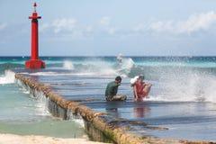 Cubaanse tieners die pretzitting op pijler van een vuurtoren hebben onder nevel van overzees royalty-vrije stock foto