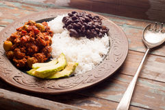 Cuban Beef Picadillo. Cuban style beef picadillo served with white rice, black beans and avocado. Served on a rustic wooden table Royalty Free Stock Images