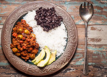 Cuban Beef Picadillo. Cuban style beef picadillo served with white rice, black beans and avocado. Served on a rustic wooden table Stock Image