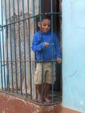 CUBAN BOY BEHIND THE WINDOW, TRINIDAD, CUBA Royalty Free Stock Photo