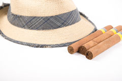 Cuban cigars and straw Panama hat. Cuban cigars and a woven straw panama hat on white background Royalty Free Stock Images