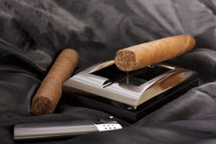 Cuban cigars. Close up of  metallic ashtray, lighter and cuban cigar on black silk background Stock Image
