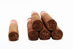 Cuban Cigars. Six Cuban Cigars isolated on white. One cigar apart. Very shallow depth of field. Front view Royalty Free Stock Photos