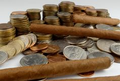 Cuban cigars with coins isolated on white Royalty Free Stock Images