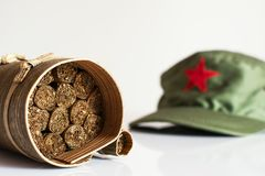 Cuban cigars rolled in banana leaf and military cap on the backg. Some Cuban cigars rolled in banana leaf and military cap on the background royalty free stock images