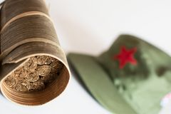 Cuban cigars rolled in banana leaf and military cap on the backg. Some Cuban cigars rolled in banana leaf and military cap on the background stock image