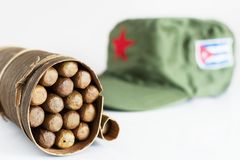 Cuban cigars rolled in banana leaf and military cap on the backg. Some Cuban cigars rolled in banana leaf and military cap on the background stock photo