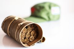 Cuban cigars rolled in banana leaf and military cap on the backg. Some cuban cigars rolled in banana leaf and military cap on the background royalty free stock image
