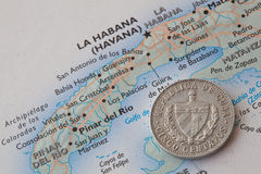 Cuban coin lying on a map Royalty Free Stock Photos