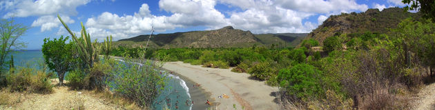 Cuban eastern landscape with a rural beach and mountains. Cuban eastern landscape with a panoramic view of a rural beach rounded by mountains and typical Stock Photos