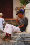 A Cuban elderly old worker Lighting up his Cigar in Cuba