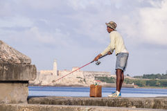 Cuban Fisherman with rod on Malecon in front of Castillo. Havana, Cuba on December 22, 2016: Fisherman with rod on Malecon in front of Castillo de los Tres Reyes Royalty Free Stock Images