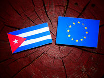 Cuban flag with EU flag on a tree stump isolated. Cuban flag with EU flag on a tree stump Royalty Free Stock Images