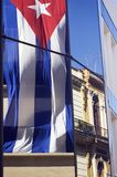 Cuban flag and modern and old facades. Reflections in the glass of a building of the Cuban flag and a colonial facade of Habana - Cuba Royalty Free Stock Images