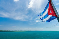 Cuban flag. Over the sea and sky Stock Photos