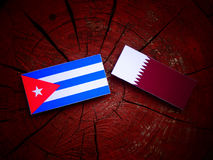 Cuban flag with Qatari flag on a tree stump isolated. Cuban flag with Qatari flag on a tree stump Royalty Free Stock Images