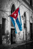 Cuban flag in a shabby street in Havana. Colorful cuban flag in a shabby black and white street in Havana Royalty Free Stock Images