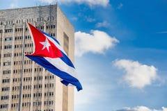 Cuban flag on a sunny day. Near a tall building stock photos