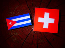Cuban flag with Swiss flag on a tree stump  Royalty Free Stock Image