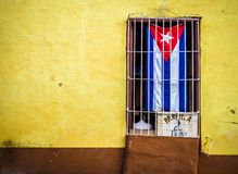 The cuban flag in a window. The cuban flag in the window of a canteen in Trinidad Royalty Free Stock Photography
