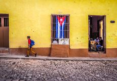 Cobblestone street in trinidad with cuban flag. The cuban flag in the window of a canteen in Trinidad with a boy passig by with matching colors Stock Image