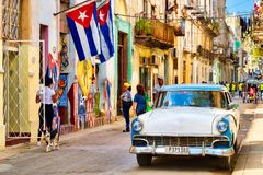 Cuban flags, classic car and colorful decaying buildings in Old Havana. HAVANA,CUBA - MARCH 16,2018 : Urban scene with cuban flags, classic car and colorful stock photo