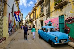 Cuban flags, old car and colorful buildings in Old Havana. HAVANA,CUBA - MARCH 16,2018 : Street scene with cuban flags, old car and colorful aged buildings in royalty free stock images