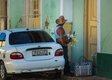 A Cuban man with a flower and car in street of Caribbean colorful colonial town, Trinidad, communism Cuba, America. Cuban people man waiting in colorful royalty free stock photography