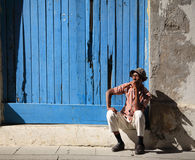 Cuban man and his cigar. Sat on a step in the streets of Havana in Cuba Stock Photography