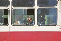 Cuban man looking through window of moving bus in Havana, Cuba Stock Photo