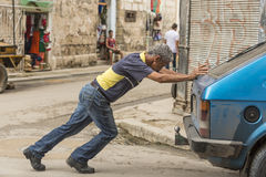 Cuban man pushing broken car Havana Stock Images