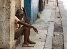 Cuban man sitting and smoking in doorway of his home in Havana Cuba royalty free stock images