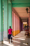 Cuban man walking through colorful passway in Havana. Havana, Cuba on December 23, 2015: Cuban man in casual pink shirt walking through a colorful passway Royalty Free Stock Photography