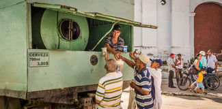 Cuban men buying beer from a truck. Sancti Spiritus, Cuba on January 1, 2016: Cuban men buying beer from a truck to celebrate New Year. Homebrew beer is popular Stock Image