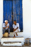Cuban men sitting in shadow on street of Trinidad and talking. Royalty Free Stock Photography