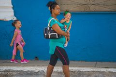Happy Old Cuban people woman and child in street of Caribbean communism Cuba, America. Cuban people woman and children walking in colorful traditional street of royalty free stock photography