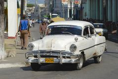 Cuban person drives vintage American car at the street of Pinar del Rio, Cuba. Royalty Free Stock Photo